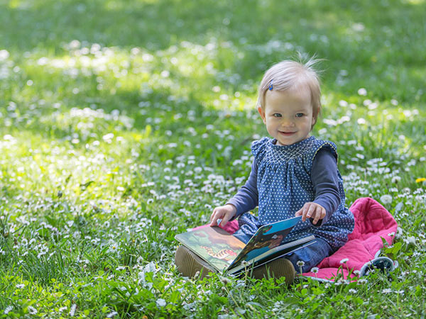 child reading cradle to cradle picture book in the meadow